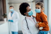 African American Pediatrician And Small Girl With Protective Face Masks At Medical Clinic.