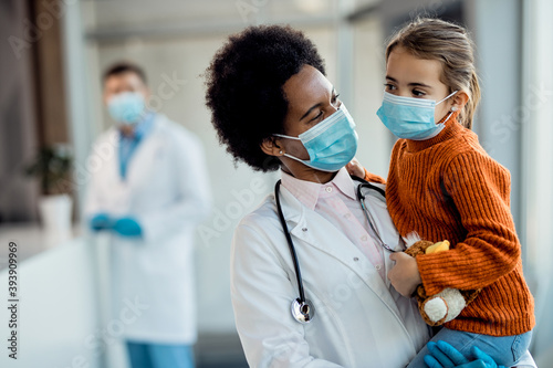 Canvas Print African American pediatrician and small girl with protective face masks at medical clinic