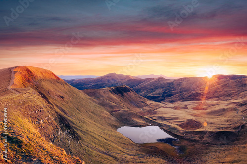 Mountain lake on sunrise time. Picturesque autumn landscape with sun in morning sky, Carpathian mountains