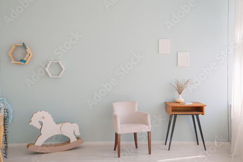 Minimalistic nursery room with side cabinet, toys and wooden horse