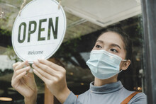 Reopen. Friendly Waitress Wearing Protection Face Mask Turning Open Sign Board On Glass Door In Modern Cafe Coffee Shop, Cafe Restaurant, Retail Store, Small Business Owner, Food And Drink Concept