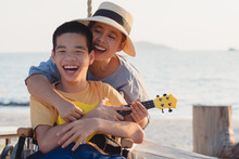 Asian Special Child On Wheelchair Is Singing, Playing Ukulele Happily On The Beach With Parent,Natural Sea Beach Background,Life In The Education Age Of Disabled Children,Happy Disability Kid Concept.