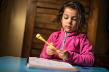 Little Girl Drawing And Doing Homerworks At Home