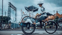 Man Riding Pedicab On Road In City