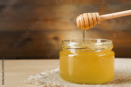 honey flowing from honey dipper into the jar on wooden background in rustic styl Fotobehang