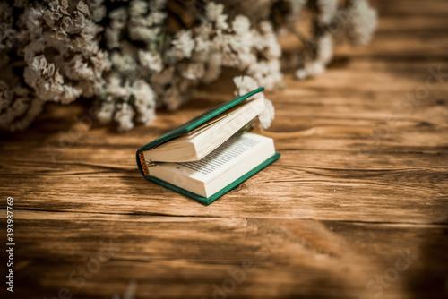 Obraz na plátně Vintage novel books with bouquet of flowers on old wood background