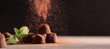 Chocolate Truffles With Mint Leaves On Wooden Table Dark Background