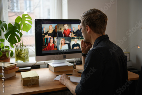 Work from home. Young man having Zoom video call via a computer in the home office. Stay at home and work from home concept during Coronavirus pandemic. Smiling handsome man teleworking - fototapety na wymiar