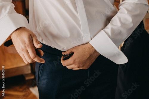Fototapeta Pan młody zakłada skórzany pasek lub dominacja mężczyzny w garniturze obraz