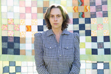 Woman In Plaid Shirt In Front Of Handmade Quilt