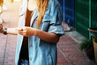 Midsection Of Woman Wearing Denim Jacket While Standing On Footpath