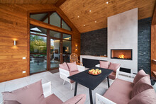 An Open Terrace With Table, Chairs, Fireplace And Apples