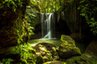 canvas print picture - Beautiful waterfall in rainforest. Tropical landscape. Slow shutter speed, motion photography. Foreground with big stones. Environment concept. Suwat waterfall, Bali, Indonesia