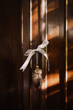 Owl Shaped Crystal Decoration With Ribbon Saying Let It Snow Hanging From Old Cabinet Door