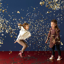 Two Happy Toddler Girls Throwing Golden Confetti