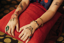Close Up Of Woman's Hands With Colorful Tattoos And Jewelry