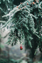 Old Fashioned Wooden Christmas Tree Decoration In The Shape Of A Santa Mouse Hanging From Frozen Fir Tree Outdoors
