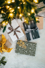 Overhead Shot Of Various Gifts On Carpet Under Christmas Tree With Shining Lights