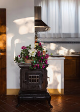 Fake Flowers Bouquet On Top Of Old Iron Stove In Kitchen