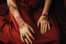 Woman's Hands Covered In Colorful Tattoos And Jewelry