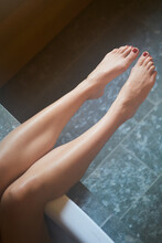 Female Legs With Feet With Red Toe Nails