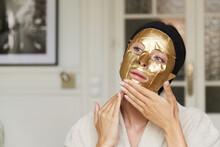 Woman Softly Applying A Golden...