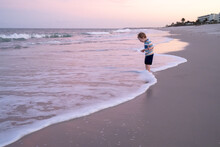 Toddler Playing On Beach In Th...