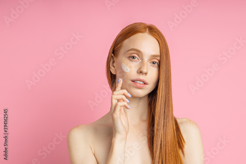 Fotografiet Closeup cropped shot of young caucasian redhead woman applying foundation, face primer or moisturizer on her face