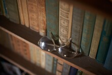Old Books And Old Glasses On The Bookshelf