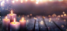 Abstract Advent - Four Purple Candles With Soft Blurry Lights And Glittering On Flames