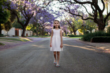 A Cute Little Girl In A White Dress Walks Down The Street With Blooming Jacaranda Trees