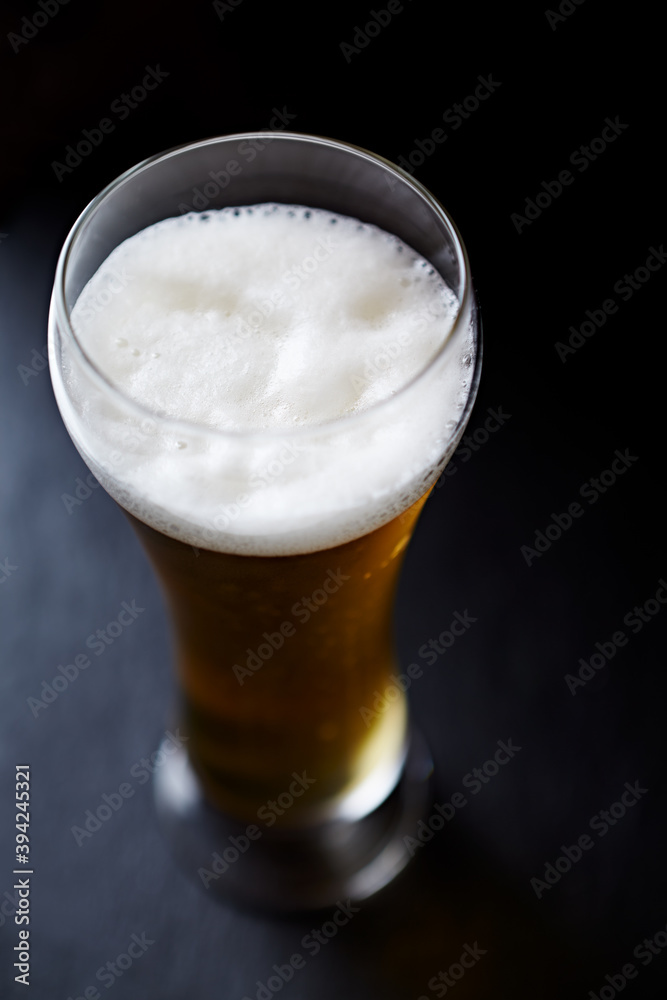 Fototapeta Glass of beer on dark background. Close up.