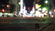 Closeup Of A Japanese Coin Stucked On The Foothpath With Bokeh City Lights In The Background.