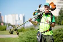Municipal Gardener Landscaper Senior Man Worker With Gas Grass Trimmer Equipment On Sunlight City Background