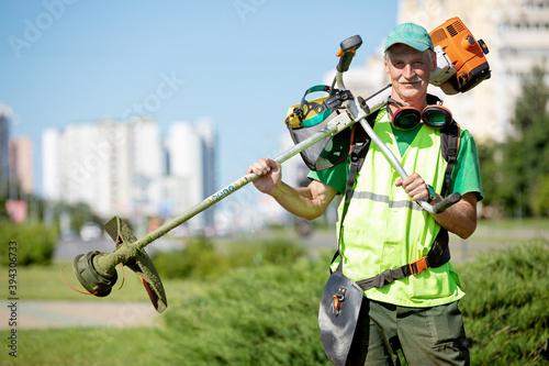 Fototapeta Municipal gardener landscaper senior man worker with gas grass trimmer equipment