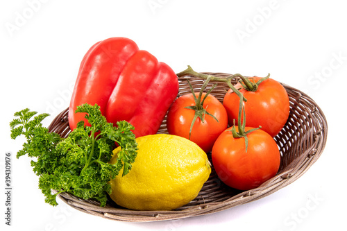 a basket of red pepper, lemon, tomatoes and parsley cooking vegetable ingredients isolated on white   © G. Socka