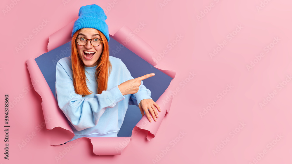 Fototapeta Glad red haired woman suggests to check this promo indicates aside on copy space poses through paper background breaks in hole wears casual blue clothes gives direction to shop with big sales