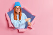 Leinwandbild Motiv Smiling ginger woman feels optimistic points away on blank space shows advertisement wears blue hat glasses and jumper breaks through paper background promots some item. Place your promotion here