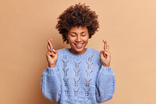 Hopeful Beautiful Young African American Woman Stands With Crossed Fingers Believes Dreams Come True Smiles Broadly Keeps Eyes Closed Wears Knitted Sweater Isolated Over Brown Studio Background