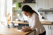 Happy Young Caucasian Woman Stand At Home Kitchen Counter Watch Webinar On Laptop Make Notes. Smiling Female Study Online On Computer At Home. Girl Make List Plan, Engaged In Time Management.