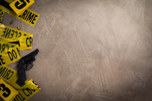 Flat Lay With Yellow Tape, Crime Scene Marker And Gun On Grey Stone Background. Space For Text