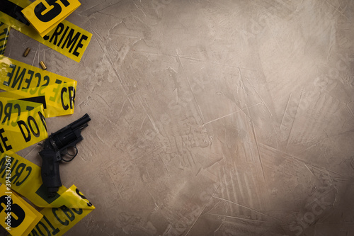 Canvas Flat lay with yellow tape, crime scene marker and gun on grey stone background
