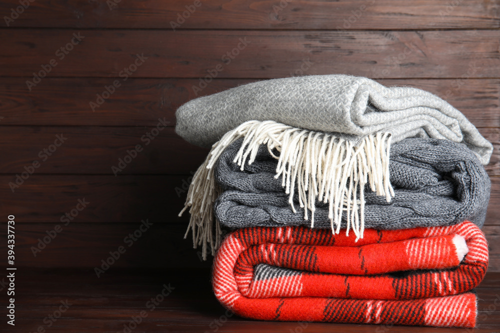 Fototapeta Stack of soft plaids on brown wooden table, space for text