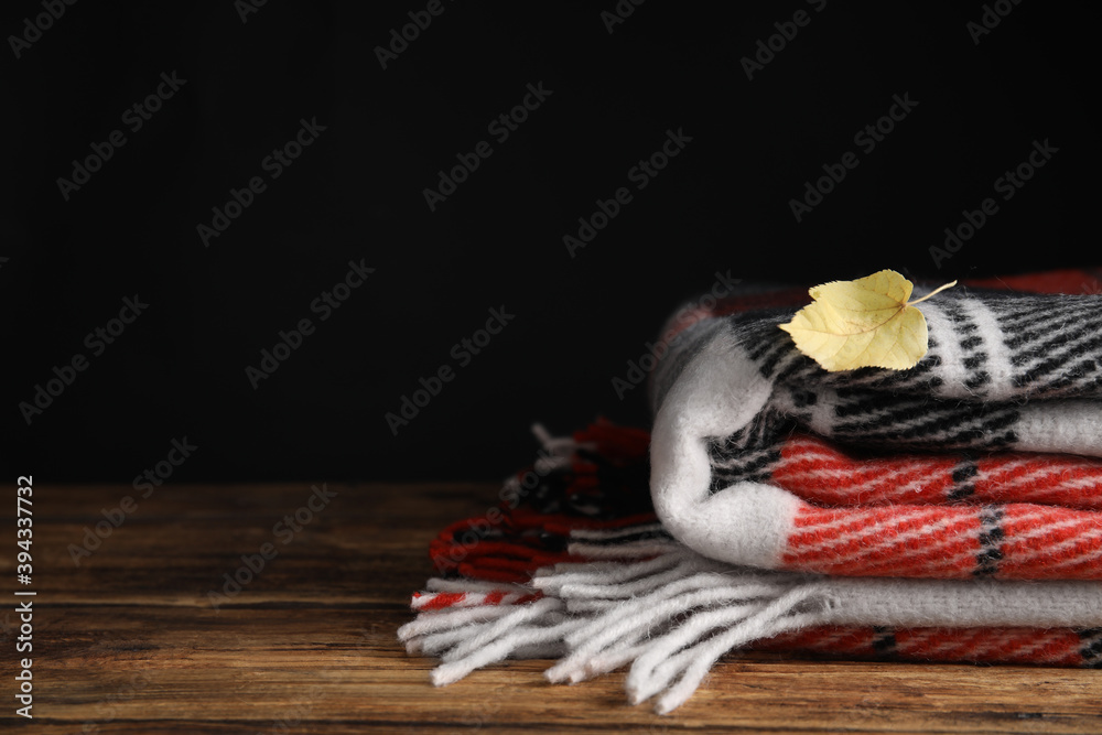 Fototapeta Checkered plaid and dry leaf on wooden table, closeup. Space for text