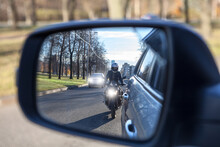 Mutual Passing, Motorcycle And Vehicle With Dazzle Lighting Overtaking The Car, View In A Side Mirror. Improper Driving Or Traffic Violation