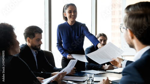 Foto Wide panoramic view of smiling young businesswoman share handout material to colleagues at office meeting