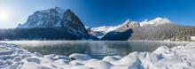 Lake Louise In Early Winter Sunny Day Morning. Mist Floating On Turquoise Color Water Surface. Clear Blue Sky, Snow Capped Mountains In Background. Beautiful Natural Landscape In Banff National Park.