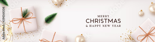 Fototapeta Christmas poster, holiday banner. Merry Christmas and Happy New Year. Xmas Background design lights garland, realistic gifts box, white balls and glitter gold confetti. Lush green tree and pine. obraz