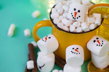 Marshmallow Snowmen On A Mint Turquoise Background With A Yellow Cocoa Mug Illuminated By A Garland
