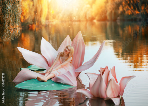 Fotografiet Happy fantasy young blonde woman little fairy princess sitting in pink lotus flower on lake water